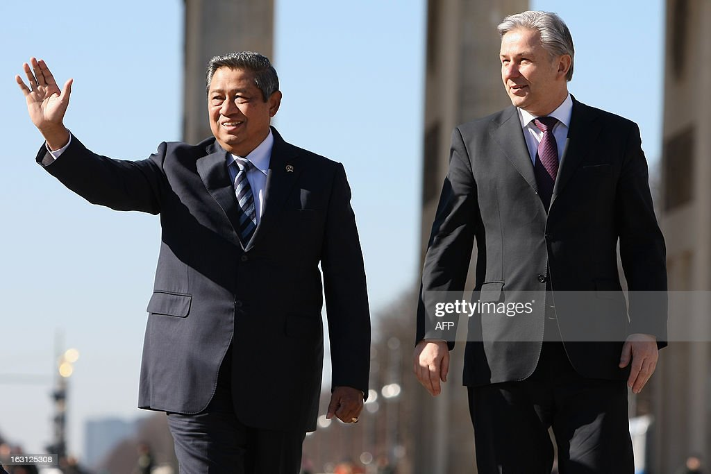 Indonesian President Susilo Bambang Yudhoyono (L) waves next to Berlin Mayor Klaus Wowereit as they walk in front of the Brandenburg Gate during his visit in Berlin on March 5, 2013. Indonesian President Susilo Bambang Yudhoyono is in Berlin to meet with Chancellor Angela Merkel and inaugurate the ITB Berlin tourism fair, one of the top industry gatherings. BERRY