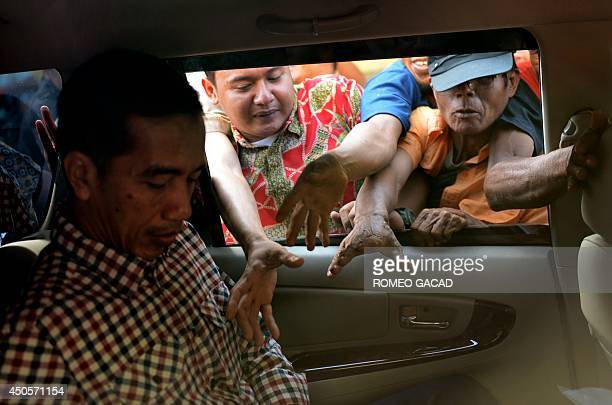 Indonesian presidential candidate and Jakarta Governor Joko Widodo prepares to hand out tshirts from his car window during a campaign rally in...