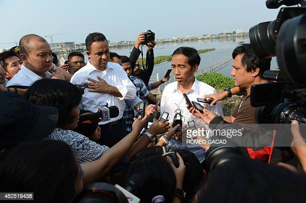 Indonesian presidential candidate Jakarta Governor Joko Widodo accompanied by spokesman Anies Baswedan is intervied by journalists at an urban...