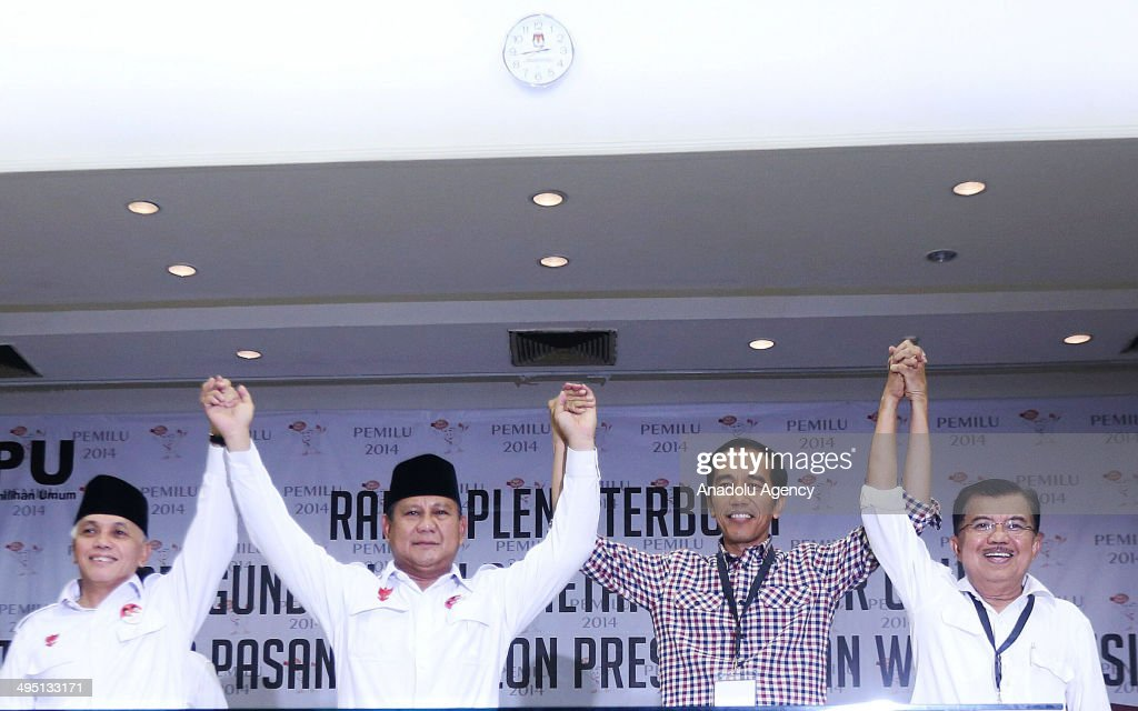 Indonesian presidential candidates Prabowo Subianto (2L) from the Gerindra Party (Great Indonesia Movement) and running mate Hatta Rajasa (L) with Joko Widodo (3L) from the Indonesian Democratic Party of Struggle (PDI-P) and running mate Jusuf Kalla (R) join hands during a ceremony at the commission on election on June 1, 2014 in Jakarta ahead of the campaign for presidential polls.