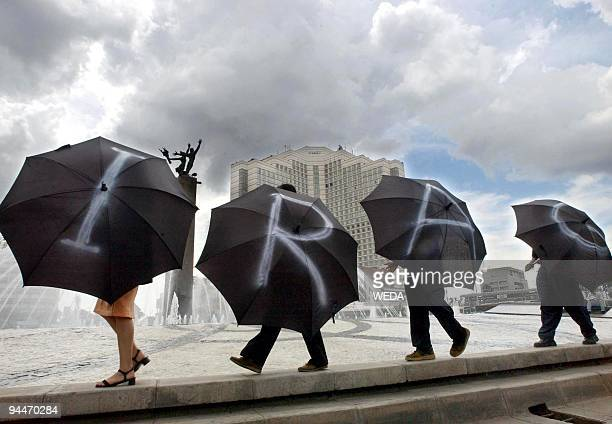 Indonesian protesters carry umbrellas displaying 'IRAQ' to protest against the USled war on Iraq during a demo outside the British embassy in Jakarta...