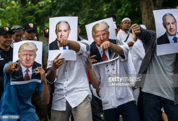 Indonesian protesters pose with cutout portraits of US President Donald Trump and Israeli Prime Minister Benjamin Netanyahu during a protest in front...