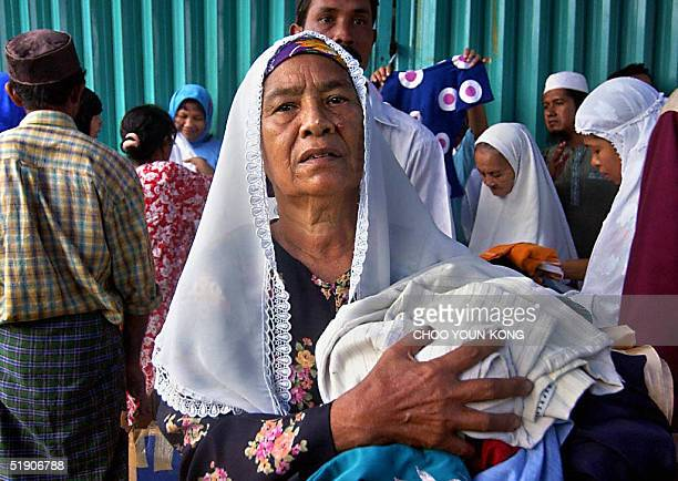 Indonesian refugees get relief goods from international and Indonesian relief organisations in Banda Aceh 01 January 2005 as the area struggles to...
