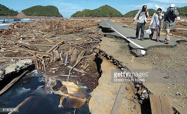 Indonesian refugees walk past the decomposing body of a man killed in the earthquake and tsunami disaster as they head to their home village to look...