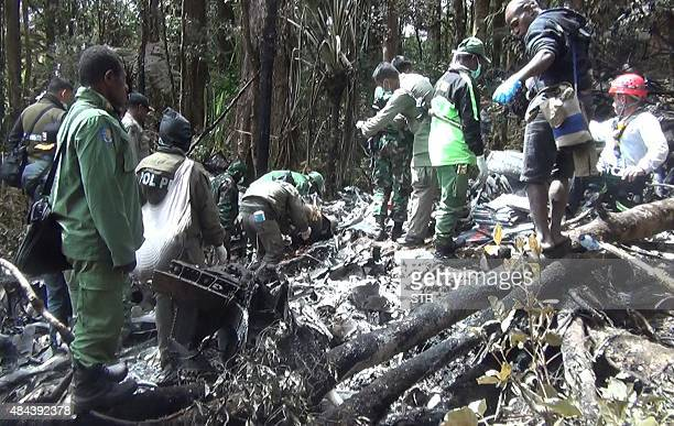 Indonesian rescuers search through wreckage of the Trigana Air ATR 42300 twinturboprop plane at the crash site in the mountainous area of Oksibil on...