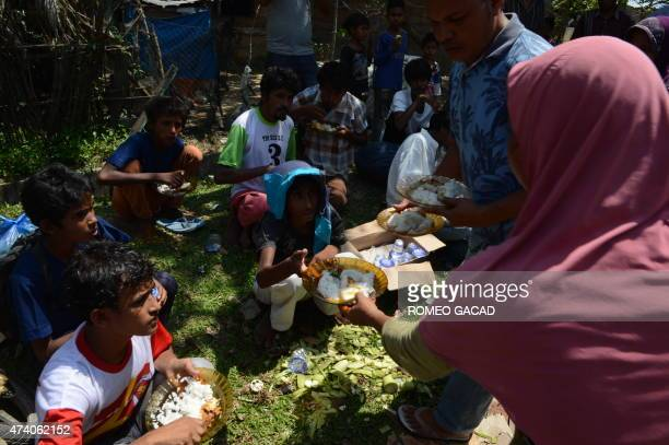 Indonesian residents hand food to a group of Rohingya men from Myanmar in the compound of a mosque in Julok district Aceh province on May 20 2015...