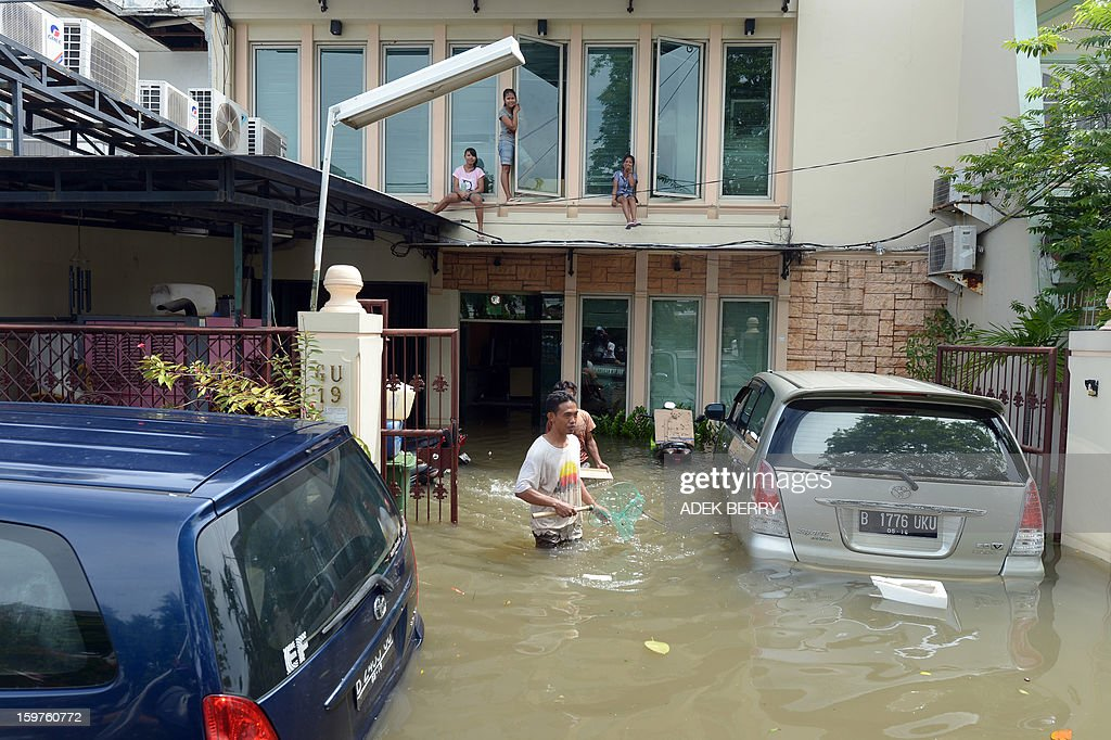 Indonesian residents stay on the second floor of a house after floodwaters submerged a luxury housing complex in Jakarta on January 20, 2013. The death toll from floods in Indonesia's capital Jakarta rose to 15 on January 19 after rescuers found another four bodies. The floods are the worst to hit the capital since 2007 and forced 18,000 people from their homes.