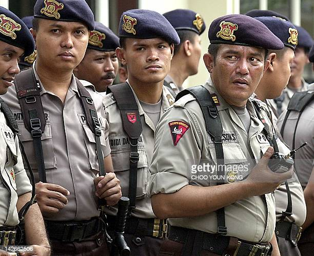 Indonesian riot police stand guard outside the court where Indonesian Muslim cleric Abu Bakar Bashir stands trial to stop any possible demonstration...