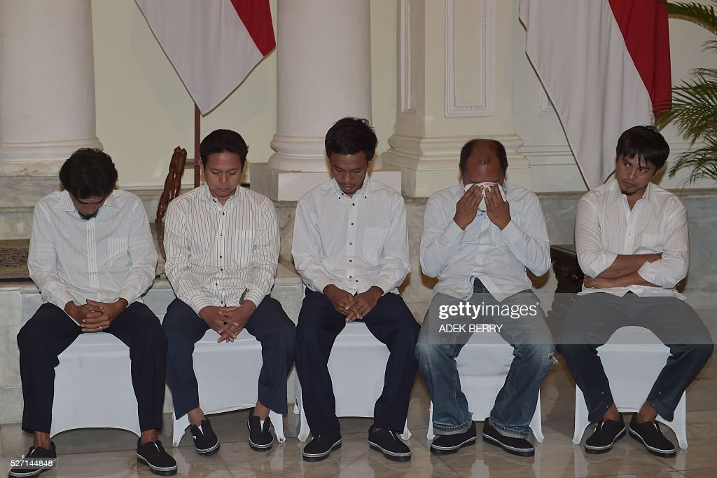 Indonesian sailors attend a ceremony to mark the hostages being handed over to thier families at the Foreign Ministry office in Jakarta on May 2, 2016, after ten Indonesian sailors held hostage by Abu Sayyaf Islamic militants returned home on May 1 after being freed in the southern Philippines, less than a week after the gunmen beheaded a Canadian captive. About five weeks after being abducted, the 10 tugboat crew turned up outside the house of the provincial governor on the remote Philippine island of Jolo. They flew back to Jakarta later the same day, arriving on a private plane at an air force base before being driven away in a minibus without speaking to reporters. / AFP / ADEK