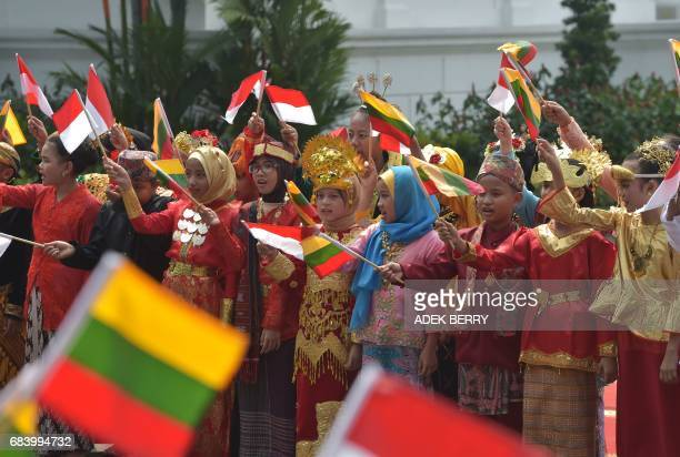 Indonesian schoolchidren welcome Lithuanian President Dalia Grybauskaite during a visit at the presidential pallace in Jakarta on May 17 2017...