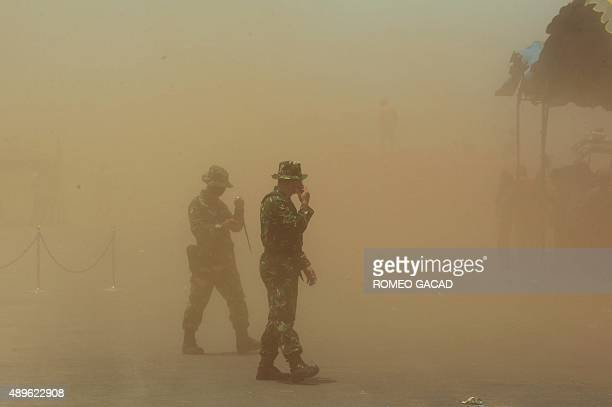 Indonesian soldiers and firefighters are engulfed in a dust cloud kicked up by a helicopter taking part in a firefighting operation on a peatland...