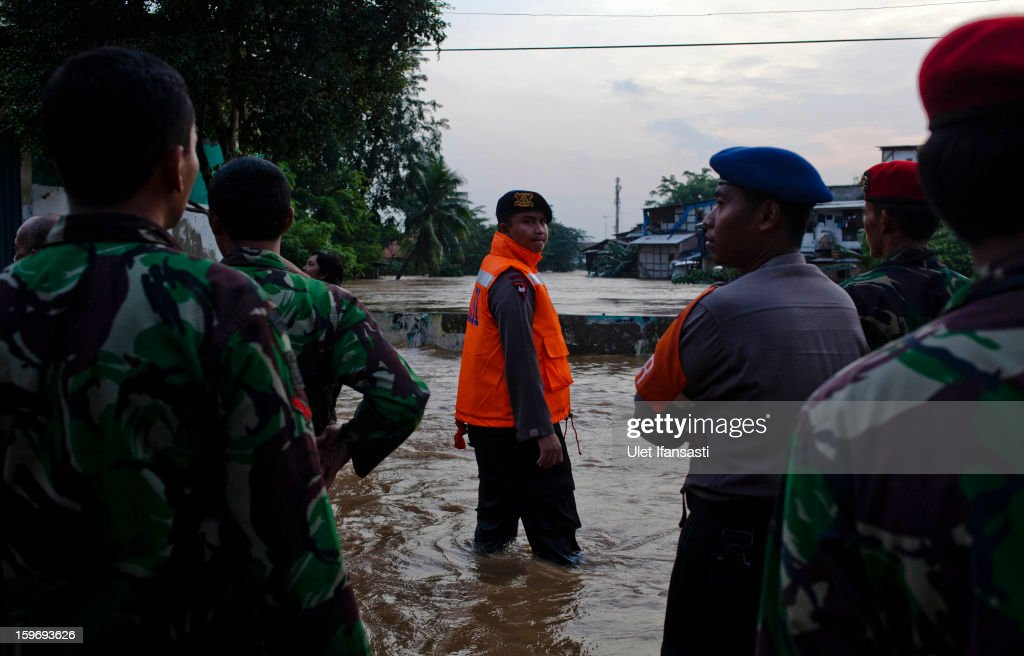 Indonesian soldiers and police stand guard as the Ciliwung River overflow in East Jakarta district on January 18, 2013 in Jakarta, Indonesia. According to the National Disaster Management Agency, about 50 percent of the capital is under water following the floods which have so far claimed eleven lives and displaced thousands of Indonesians.