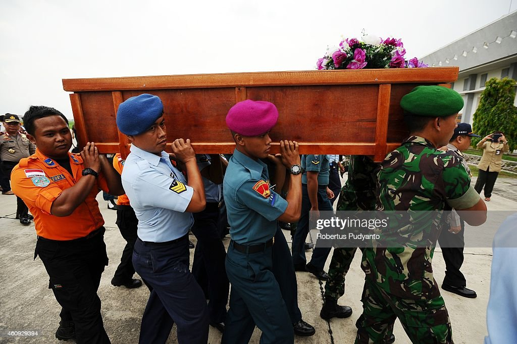 Indonesian soldiers carry coffins containing victims of the AirAsia flight QZ8501 crash at the Indonesian Air Force Military Base Operation Airport...