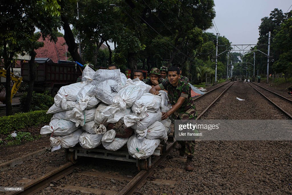 Indonesian soldiers carry sandbags to repair a collapsed canal dike in Central Jakarta district on January 18, 2013 in Jakarta, Indonesia. According to the National Disaster Management Agency, about 50 percent of the capital is under water following the floods which have so far claimed eleven lives and displaced thousands of Indonesians.