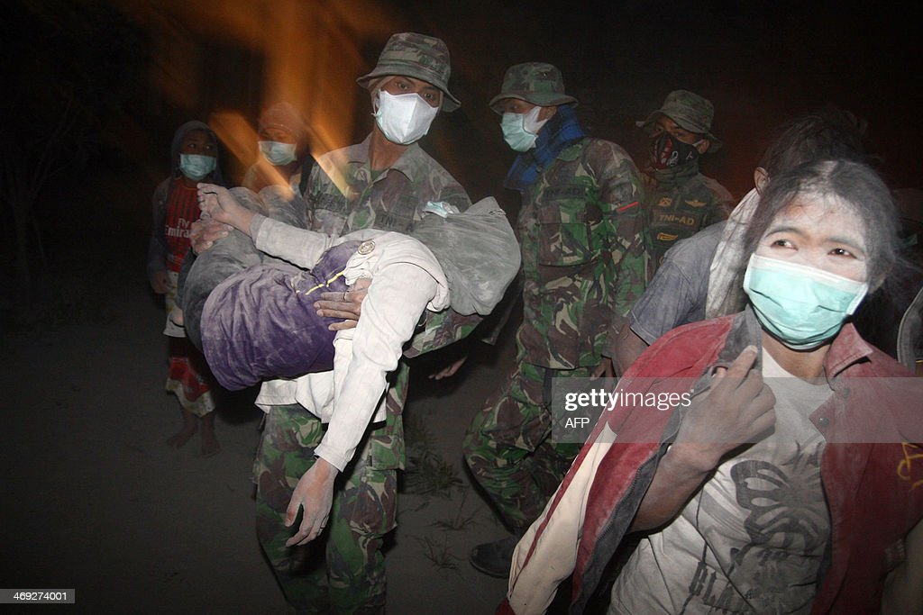 Indonesian soldiers evacuate ash covered residents in Malang, East Java province on February 14, 2014 moments after Mount Kelud, considered one of the most dangerous volcanoes on densely populated Java, erupted. Hundreds of thousands of Indonesians were ordered to evacuate and three international airports were closed on February 14 after a volcano on the main island of Java erupted spectacularly, hurling red-hot ash and rocks.