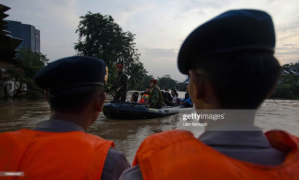 Indonesian soldiers evacuate people by rubber dinghy as the Ciliwung River overflows in East Jakarta district on January 18, 2013 in Jakarta, Indonesia. According to the National Disaster Management Agency, about 50 percent of the capital is under water following the floods which have so far claimed eleven lives and displaced thousands of Indonesians.