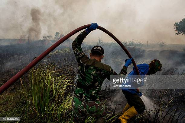 Indonesian soldiers extinguish the fire on burned peatland and fields at Sungai Rambutan village Ogan Ilir district on October 2 2015 in Palembang...