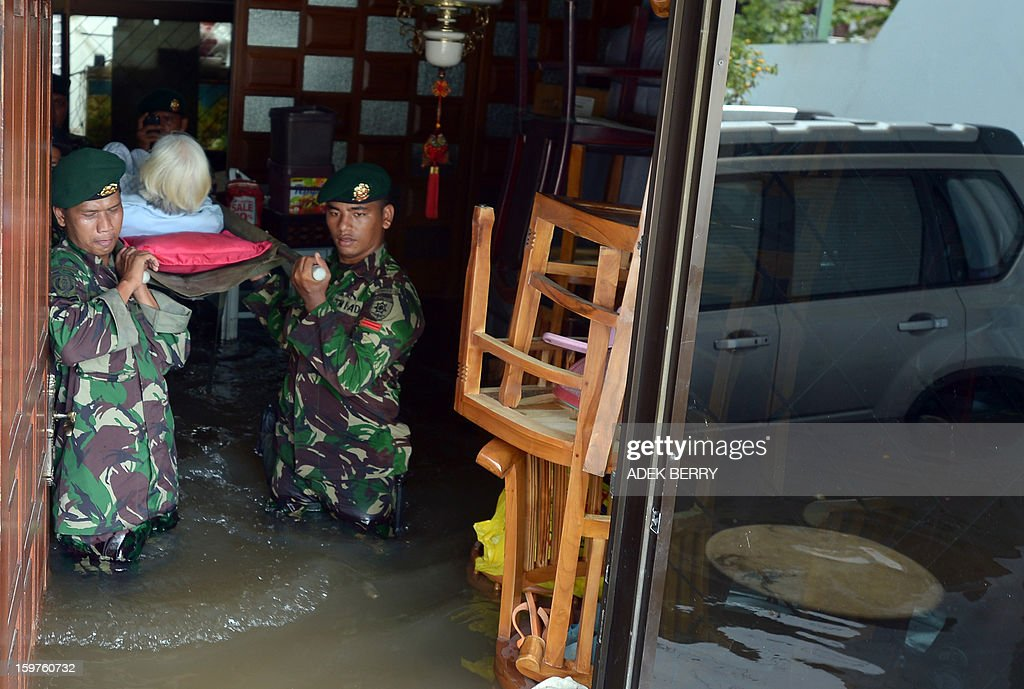 Indonesian soldiers from the Yon Kes Kostrad carry ailing elderly 87-year-old Loe Giok Tin (2nd L) from her flooded luxury housing complex in Jakarta on January 20, 2013. The death toll from floods in Indonesia's capital Jakarta rose to 15 on January 19 after rescuers found another four bodies. The floods are the worst to hit the capital since 2007 and forced 18,000 people from their homes.