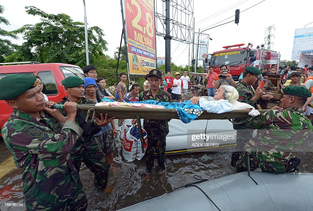 Indonesian soldiers from the Yon Kes Kostrad carry ailing elderly 87-year-old Loe Giok Tin (C) after evacuating her from a flooded luxury housing complex in Jakarta on January 20, 2013. The death toll from floods in Indonesia's capital Jakarta rose to 15 on January 19 after rescuers found another four bodies. The floods are the worst to hit the capital since 2007 and forced 18,000 people from their homes.