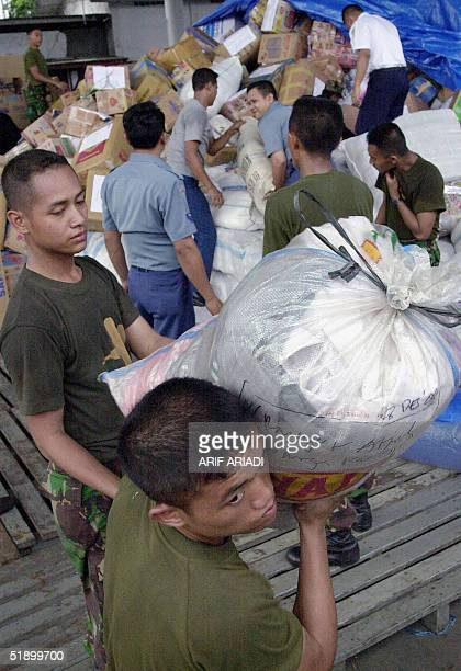 Indonesian soldiers load packages of donations in Jakarta 29 December 2004 for Aceh province following the massive 90 magnitude earthquake and...