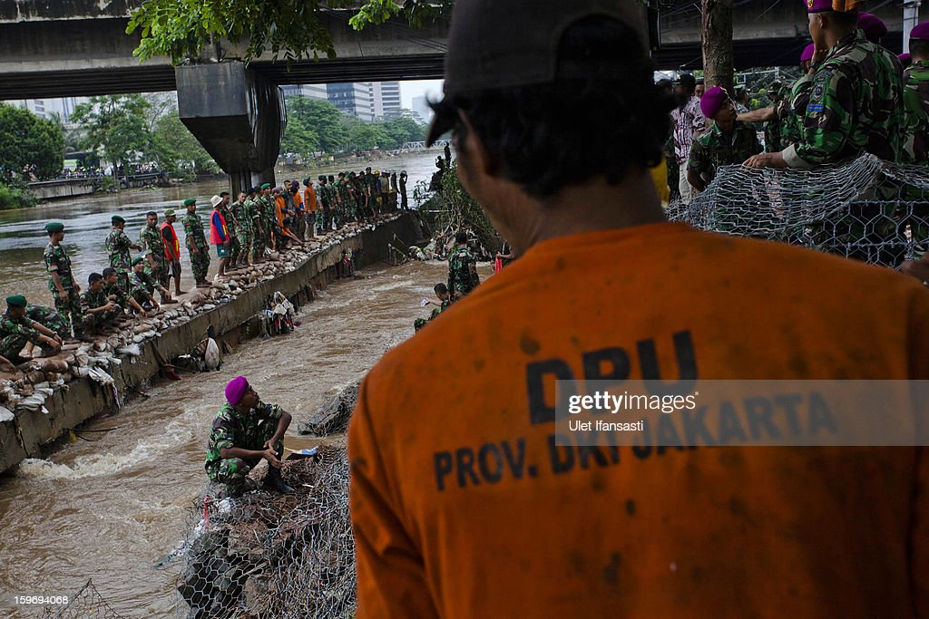 Indonesian soldiers repair a collapsed canal dike in Central Jakarta district on January 18, 2013 in Jakarta, Indonesia. According to the National Disaster Management Agency, about 50 percent of the capital is under water following the floods which have so far claimed eleven lives and displaced thousands of Indonesians.