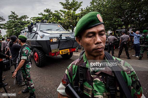 Indonesian soldiers stand guard as an Indonesian police armored vehicle carrying the Bali Nine duo Andrew Chan and Myuran Sukumaran arrive at Wijaya...