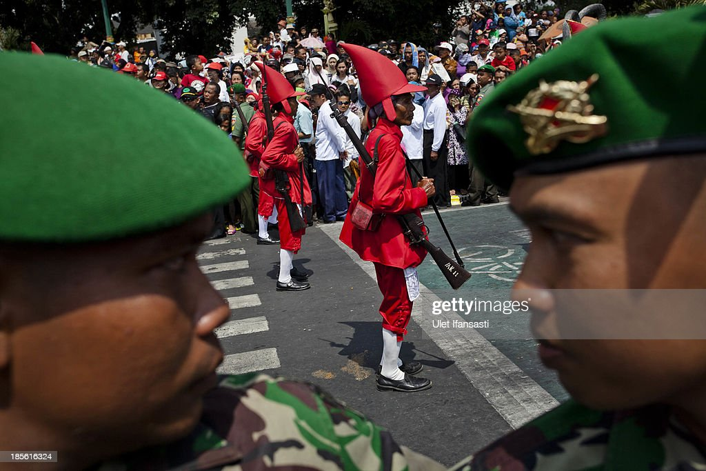 Indonesian soldiers stand guard as Kraton palace soldiers take part during the wedding ceremony parade as part of the Royal Wedding Held For Sultan Hamengkubuwono X's Daughter Gusti Ratu Kanjeng Hayu And KPH Notonegoro on October 23, 2013 in Yogyakarta, Indonesia. Wedding celebrations will take place between October 21-23 October. The wedding parade will include 12 royal horse drawn carriages and will be streamed live on the internet so that it can be watched by people all over the world.