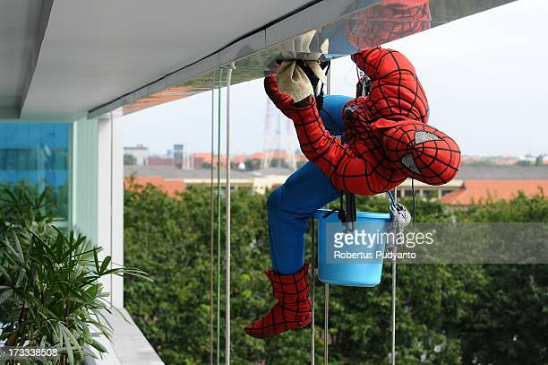 Indonesian 'SpiderMan' window cleaner 37yearold Teguh cleans the glass windows of the 18storey Alana Hotel on July 12 2013 in Surabaya Indonesia...