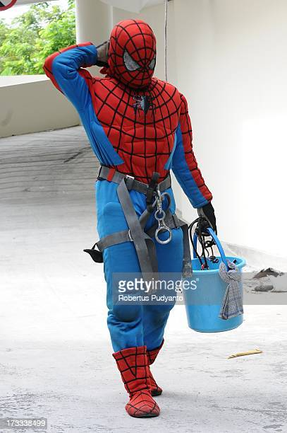 Indonesian 'SpiderMan' window cleaner 37yearold Teguh is seen after cleaning the glass windows of the 18storey Alana Hotel on July 12 2013 in...
