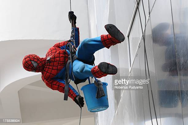 Indonesian 'SpiderMan' window cleaner 37yearold Teguh is seen lowering himself to the ground after cleaning the glass windows of the 18storey Alana...
