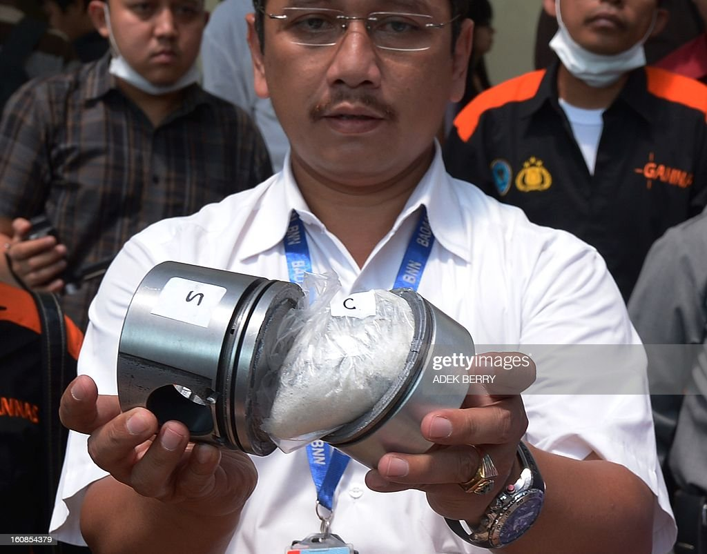 Indonesian spokesman of the National Anti-drugs Agency (BNN) Sumirat Dwiyanto shows how metahamphetamine hydrocloride also known as shabu is packed by drugs syndicate in an automotive piston engine component after it was seized last January at the Indonesian custom during a press conference in Jakarta on February 7, 2013. Indonesian authorities on February 7, destroyed about 3 kilograms of shabu confiscated during recents anti-drugs operation where syndicates are using women as drugs couriers. AFP PHOTO / ADEK BERRY