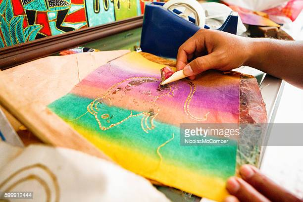 Indonesian street artist's hands making batik art