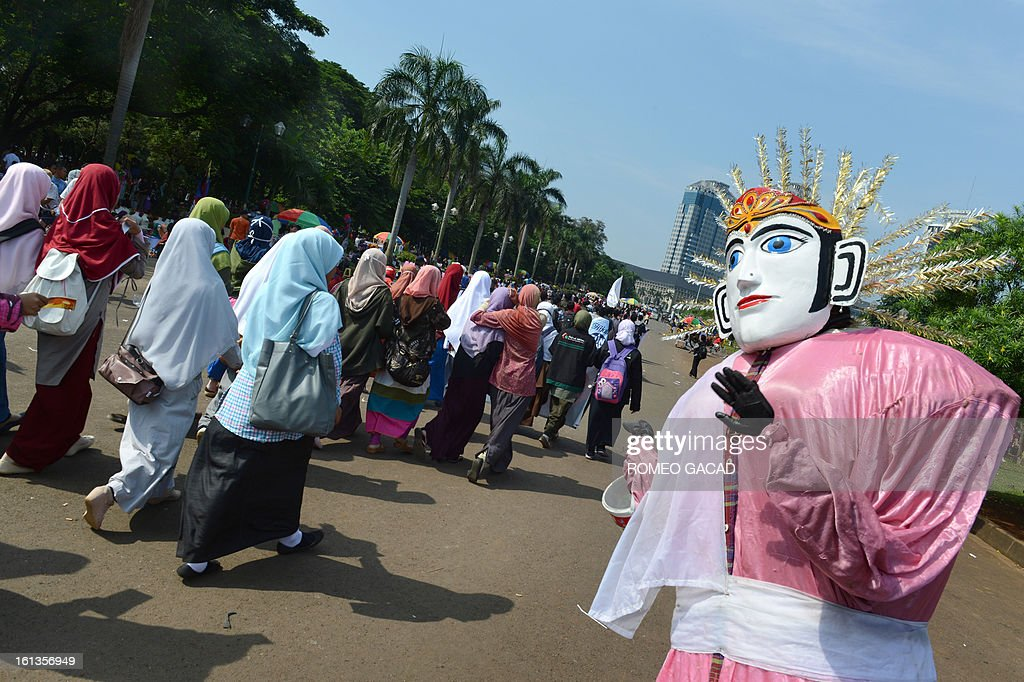Indonesian students from different universities pass a traditional ondel-ondel effigy while distributing 'hijabs' to women at the central National Monument park in Jakarta on February 10, 2013 during a campaign to promote the wearing of the hijab, a veil to cover the head as part of Islamic religious devotion for women. Indonesia is the world's most populous Muslim country, 90 percent of Indonesia's population of 240 million identify themselves as Muslim but the vast majority practise a moderate form of Islam. AFP PHOTO / ROMEO GACAD