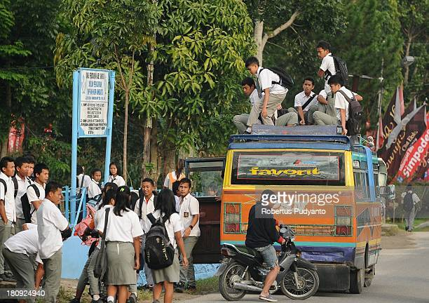 SAMOSIR SUMATRA INDONESIA SEPTEMBER 18 Indonesian students travel atop an overloaded bus on a school run in Simanindo Regency on September 18 2013 in...