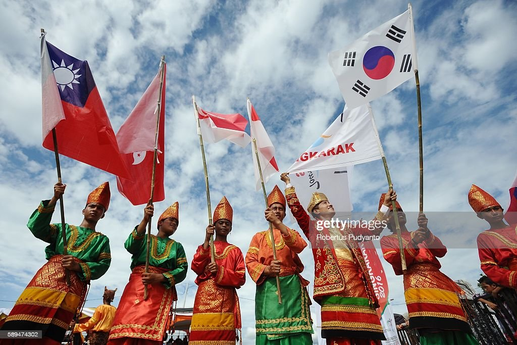 Indonesian students wearing Sumatrans traditional costumes rise the flags during closing ceremony stage eight of the 2016 Tour de Singkarak...