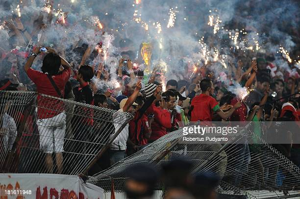 Indonesian supporters burn flares during the AFF U19 Cup Final match between Indonesia and Vietnam at Gelora Delta Stadium on September 22 2013 in...