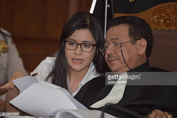 Indonesian suspect Jessica Kumala Wongso talks to her lawyer Otto Hasibuan during her trial at the Central Jakarta court in Jakarta on September 26...