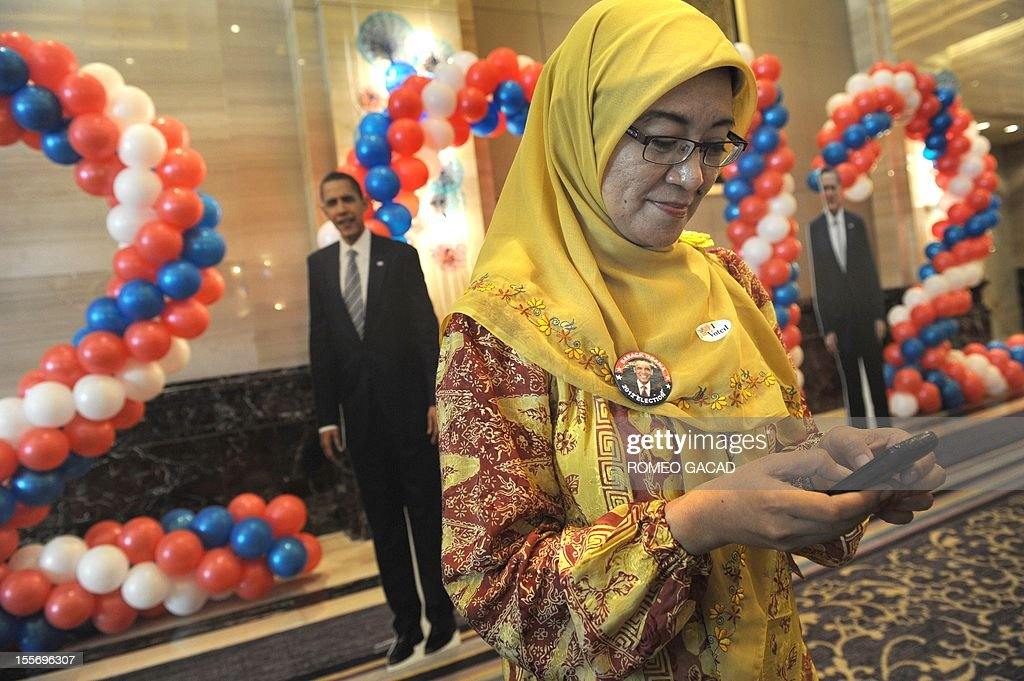 Indonesian teacher Atti Herawati, a supporter of US President Barack Obama, arrives at the poll monitoring center set up by the US embassy in Jakarta on November 7, 2012. Surveys indicate Indonesia the world's most populous Muslim country favors President Barack Obama who spent four years of his childhood in Jakarta over Republican rival Mitt Romney. In the background are the life size portraits of Obama and Romney.
