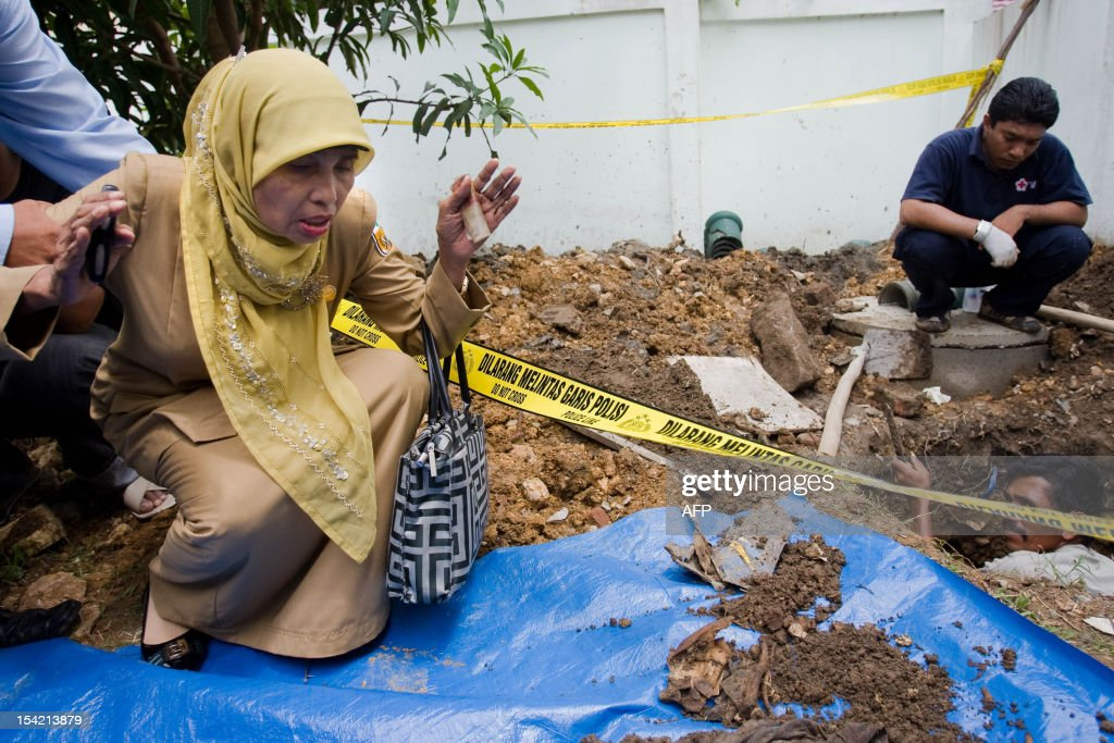 Indonesian teacher Murliani grieves as police forensic experts recover the remains of his missing brother Mursidi Ibrahim in Banda Aceh in Aceh province on October 16, 2012. Ibrahim who was missing for nearly eight years following the December 26, 2004 tsunami was identified through a recovered national identification card after workers digging wells accidentally found the remains. The 2004 Indian Ocean tsunami killed 170,000 people and entire towns flattened in Aceh province located in the northern tip of Indonesia's Sumatra island.