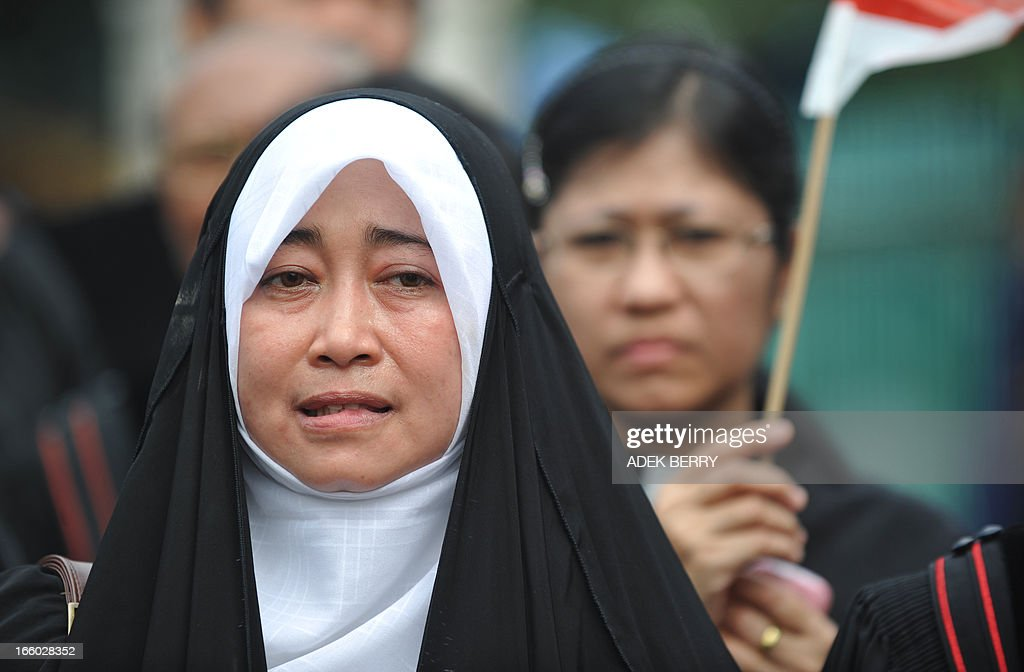 Indonesian teacher of Shiite Islamic sect Nike (L) attends a protest against Indonesian government failures to guarantee freedom of religion in Jakarta on April 8, 2013. Around 200 Indonesian minority leaders protested against religious intolerance and discrimination in the Muslim-majority country. The group representing Christians, Ahmadiyah and Shiite Islamic minority sects gathered outside the parliament, singing the country's national anthem and shouting 'We have rights' and 'Stop intolerance'. AFP PHOTO / ADEK BERRY