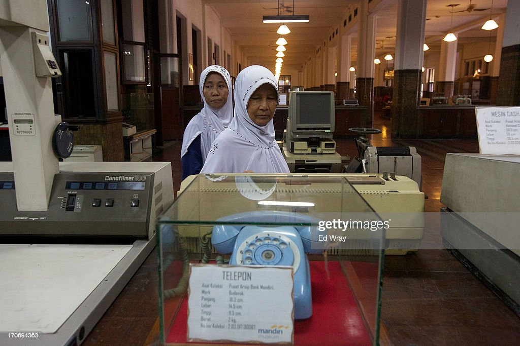 Indonesian tourists look over examples of old office equipment at the Museum Mandiri banking museum in Kota Tua Sunday June 16, 2013 in Jakarta, Indonesia. Once known as the 'Queen of the East', Kota Tua, which means Old Town in Indonesian, is the original city of Jakarta built by the Dutch in the 16th century and called Batavia at that time. Currently, Kota Tua's beautiful Colonial architecture is in ruins, abandoned as the city edged farther south over the years. Jakarta's Governor, Joko Widodo, hopes to make it a priority to restore the old town and develop it into a high end tourist destination..