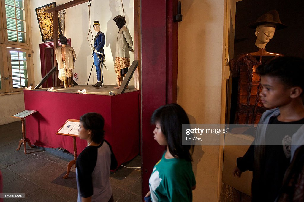 Indonesian tourists walk past a tableau at the National History museum in Kota Tua Sunday June 16, 2013 in Jakarta, Indonesia. Once known as the 'Queen of the East', Kota Tua, which means Old Town in Indonesian, is the original city of Jakarta built by the Dutch in the 16th century and called Batavia at that time. Currently, Kota Tua's beautiful Colonial architecture is in ruins, abandoned as the city edged farther south over the years. Jakarta's Governor, Joko Widodo, hopes to make it a priority to restore the old town and develop it into a high end tourist destination..