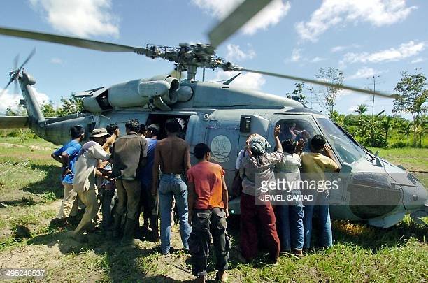 Indonesian tsunami disaster victims beleaguer a US Seahawk helicopter to get some relief goods in Suak Beka west coast of Aceh province 14 January...