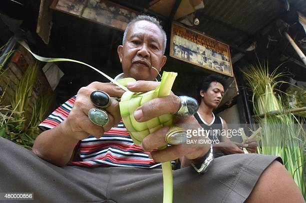 Indonesian vendors prepare ketupat a shell made from a fresh coconut leaves used to make traditional rice cakes which are popular during Eid alFitr...