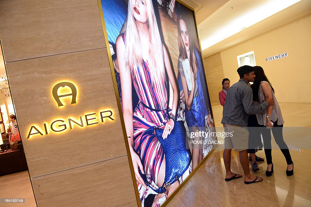 Indonesian visitors greet in front of a high-end fashion shop at an upscale mall in the capital city of Jakarta on March 20, 2013.