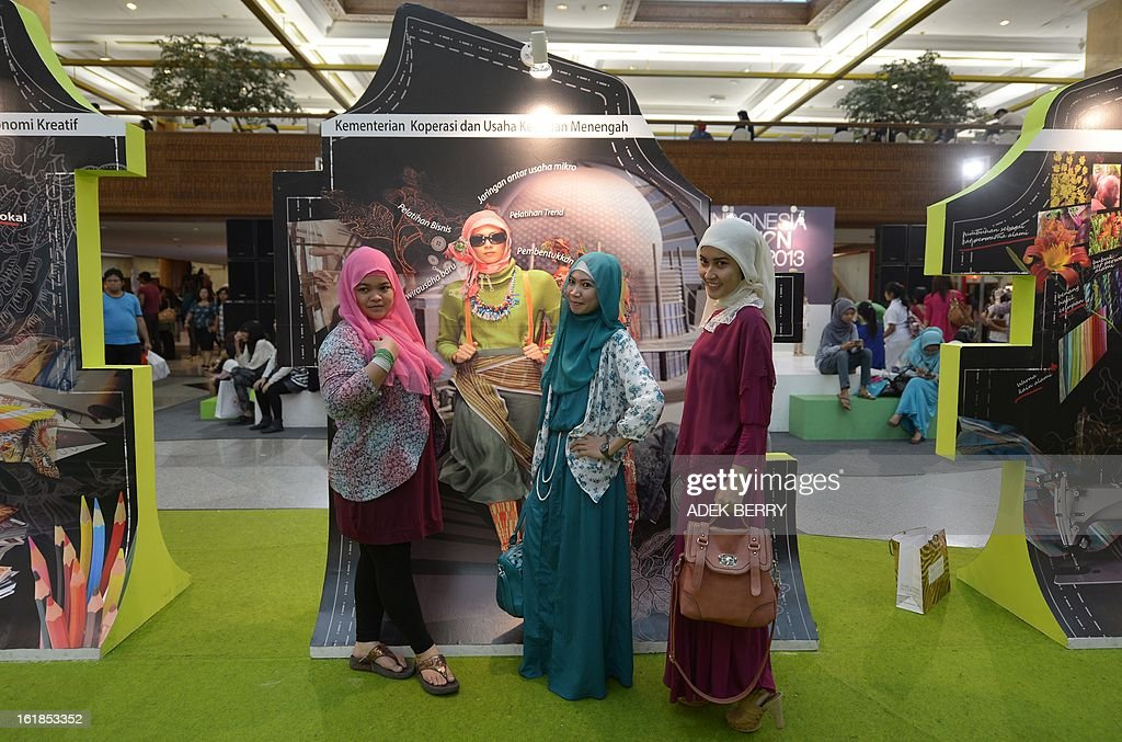 Indonesian visitors pose next to a poster featuring the 2013 Jakarta Fashion Week in Jakarta on February 17, 2013. Indonesian Minister of Tourism and Creative Economy, Mari Elka Pangestu said the country's fashion industry contributed 164 trillion rupiah (USD 17 billion) to the national gross domestic product in 2012, a significant surge from just Rp 28 trillion in 2010, while overall the creative economy sector contributed Rp 570 trillion in 2012 from Rp 437 trillion in 2010. AFP PHOTO / ADEK BERRY