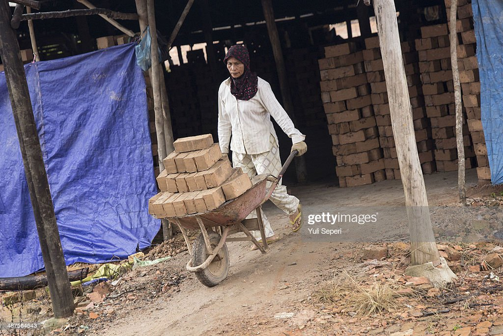Indonesian woman Nurhamsiah, pushes a wheelbarrow of bricks at Tobong Bata factory on May 1, 2014 in Bintan Island, Indonesia. Protesters across Indonesia have organised rallies to demand higher wages, as Indonesia recognises its first a national labour day holiday.