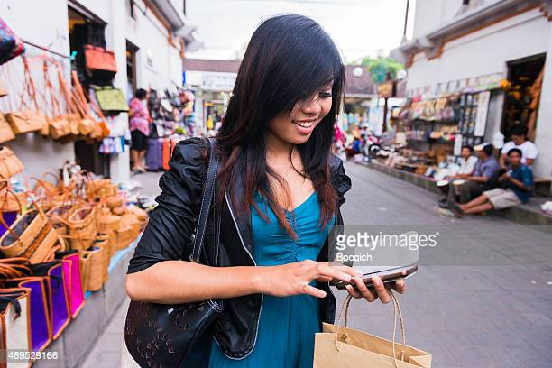 Indonesian Woman Texting in Outdoor Ubud Shopping Market Bali