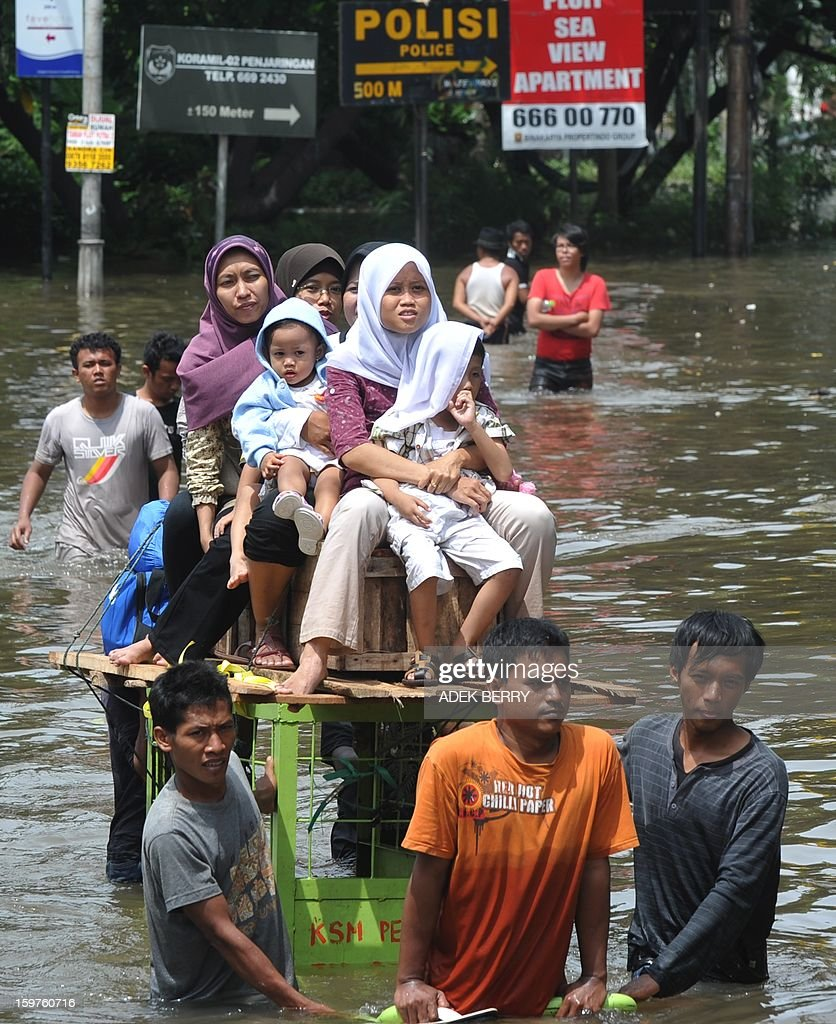 Indonesian women and children ride a rental cart pulled by men as they wade down flooded street at a luxury housing complex in Jakarta on January 20, 2013. The death toll from floods in Indonesia's capital Jakarta rose to 15 on January 19 after rescuers found another four bodies. The floods are the worst to hit the capital since 2007 and forced 18,000 people from their homes.