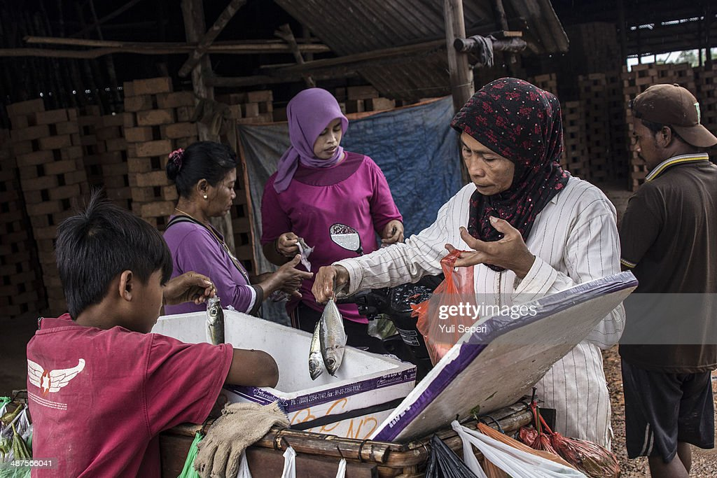 Indonesian women buy fresh fish after working to make bricks at the Tobong Bata factory on May 1, 2014 in Bintan Island, Indonesia. Protesters across Indonesia have organised rallies to demand higher wages, as Indonesia recognises its first a national labour day holiday.